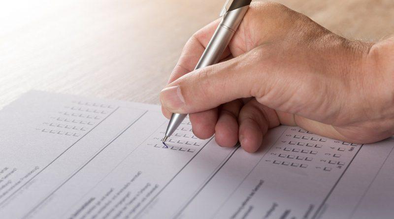 Bild von Hand mit Stift, die Umfragebogen ausfüllt.